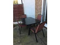 Glass topped patio table and 6 red chairs,