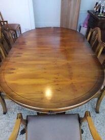 Yew reproduction dining table and eight chairs including two carvers