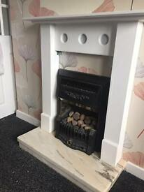 Gas fire with marble hearth and white surround.