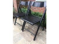 Two black wooden folding chairs, can hang on wall. Useful for spare