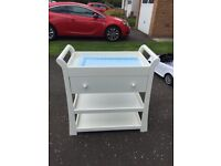 White wooden baby changing table with drawer and storage.