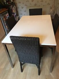 White Dining Table with silver legs plus 4 wicker chairs. All in excellent condition.