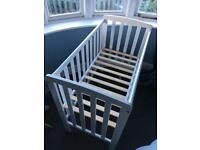 Small white wooden cot with mattress