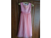 Girls bridesmaid dresses in Coral.(John Lewis)
