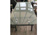 Extendable glass dining table with 6 white faux leather chairs