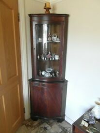 A corner display cabinet with lower cupboard and glass shelves to display cupboard