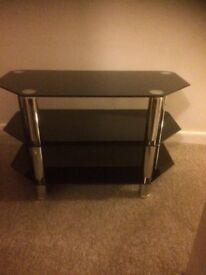 Glass TV stand . Good condition . Collection only