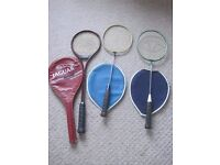 Two adult badminton racquets with covers and one Squash racquet with case.
