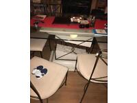 Glass top dining table with 6 cast iron chairs