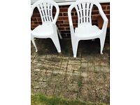 2 large white plastic chairs