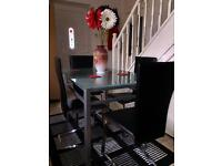 Glass table with with 4 black leather chairs in very good condition