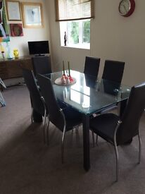 Glass dinning table with leather chairs