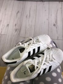 Black and white adidas superstars
