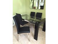 Glass table and four leather chairs.