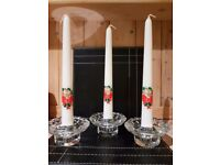 3 christmas candles in clear crystal glass holders.
