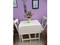 White wooden square dining table and two matching chairs