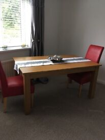 Oak affect table with two red chairs