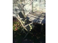 Large round garden table and three chairs in teak. Basically sound but it need of TLC