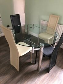 Excellent condition glass dining room table with 4 leather chairs. Table extends to circle shape.