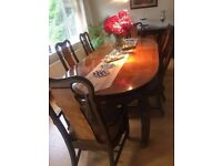 Extendable wooden dining table set with eight chairs and sideboard