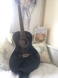 Black acoustic guitar with case and other accessories