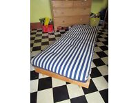 Ikea wooden futon with blue and white striped mattress