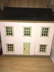 Pink dolls house with lots of wooden accessories for the rooms.