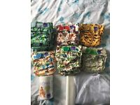 12 used Bambino mio solo reusable nappies, liners, sanitiser, nappy bin and washing nets