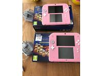 2x pink Nintendo ds with boxes chargers and games