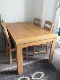 Lovely contemporary dining room table and four chairs, can seat six