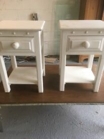 A pair of wooden bedside tables painted white
