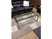 Coffee table with glass top and metal chrome legs and frame.