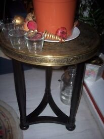 Antique oriental brass accent top table having a carved wooden base. Coffee table. Occasional table.