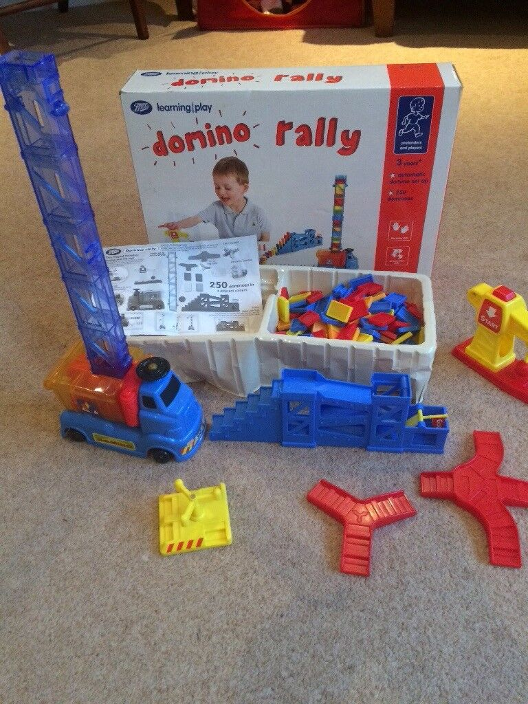 Domino Rally with battery operated vehicle which stands dominoes up as it drives