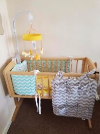 Mothercare swinging crib with sheets and a mobile