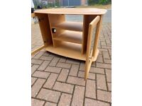 tv unit in beech wood with shelves in the centre and glass doors