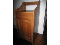 Waxed pine side or bedside table with lift up top and useful storage compartment with door.