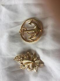 2 gold coloured broaches