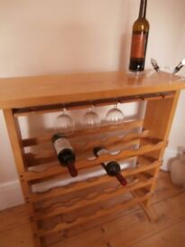 Storage and display for 24 bottles and 12 glasses on smart light wood rack.