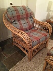A pair of wicker chairs and a matching footstool.