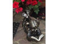 Lovely little girl reading book statue