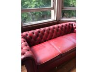 Two red leather chesterfield sofas