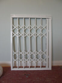 Window security grilles for sale. White sliding security shutters with attachments and locks.