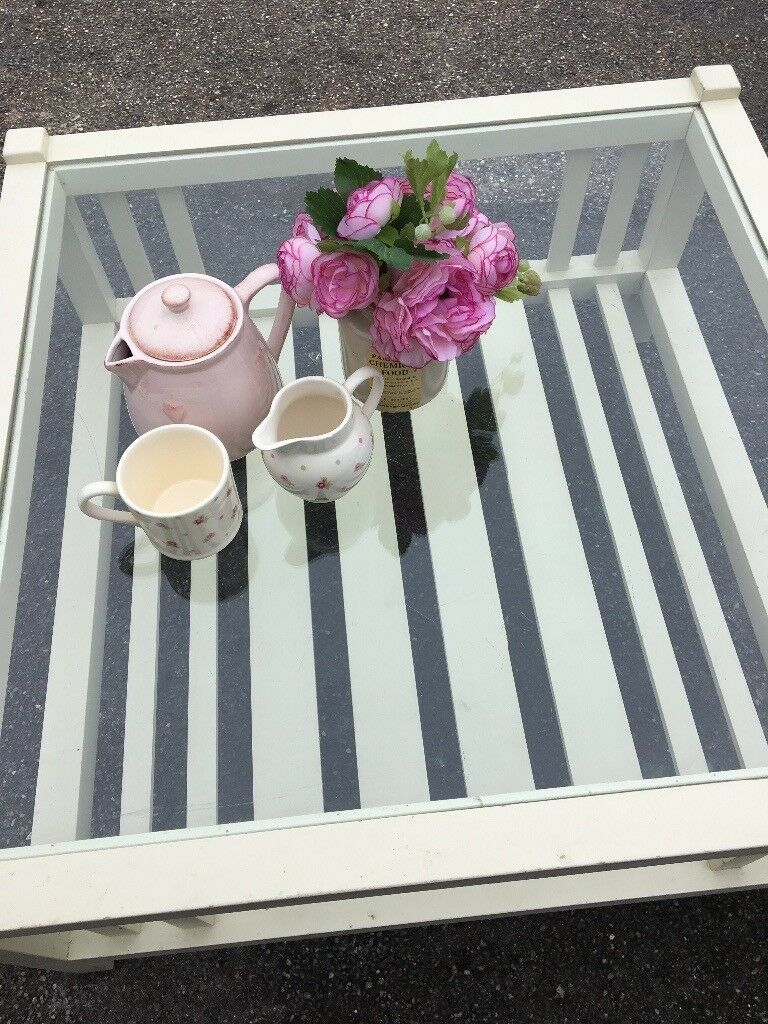 Lovely square cream coffee table. Glass top.