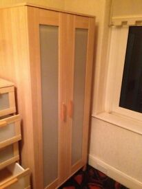 Bedroom wardrobe, bedside set of drawers and tallboy with five drawers.