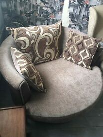 Brown swivel chair with cushions and pouffe