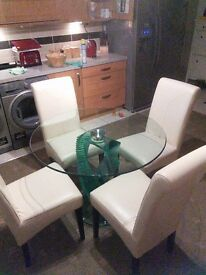 Dining Table & 4 Faux Leather Ivory Chairs in great condition. Solid glass toughened with base