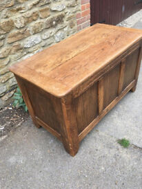 An OAK COFFER of panelled form with hinged lid enclosing candle box