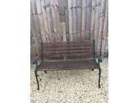 Wooden garden bench with wrought iron frame