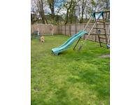 Climbing frame with slide, swings and climbing rope.
